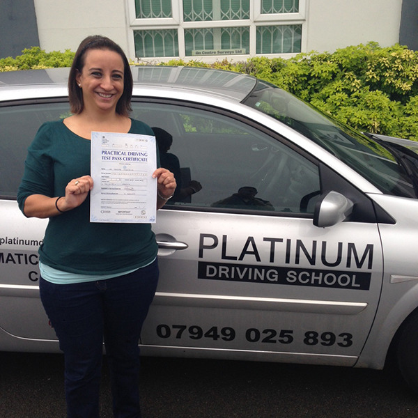 Female learner driver just passed driving test, standing next to Platinum Driving School automatic car